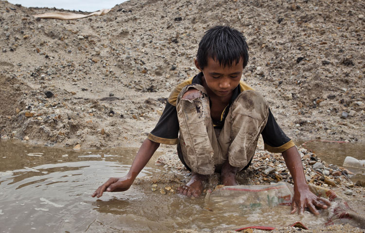 Febri Andika, a young tin miner, searches for tin ore at a mine in Belo Laut village.